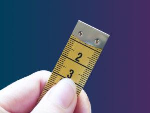 Hakukoneoptimointi lyhyesti: henkilöllä on sormissaan 3cm mittanauhaa.